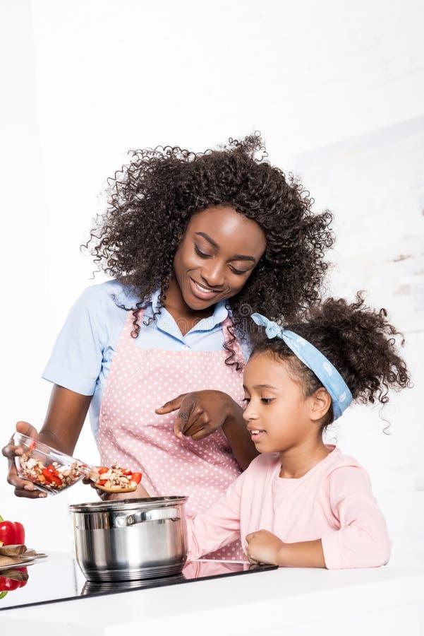 投入ingredientes的微笑的非裔美国人的母亲和女儿在平底深锅 库存图片