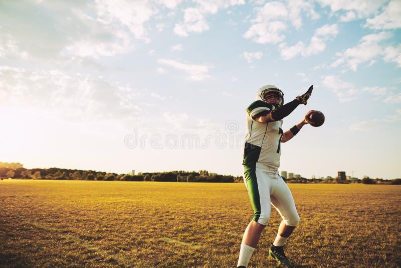 投出一张长的通行证的橄榄球四分卫在队实践期间 库存图片