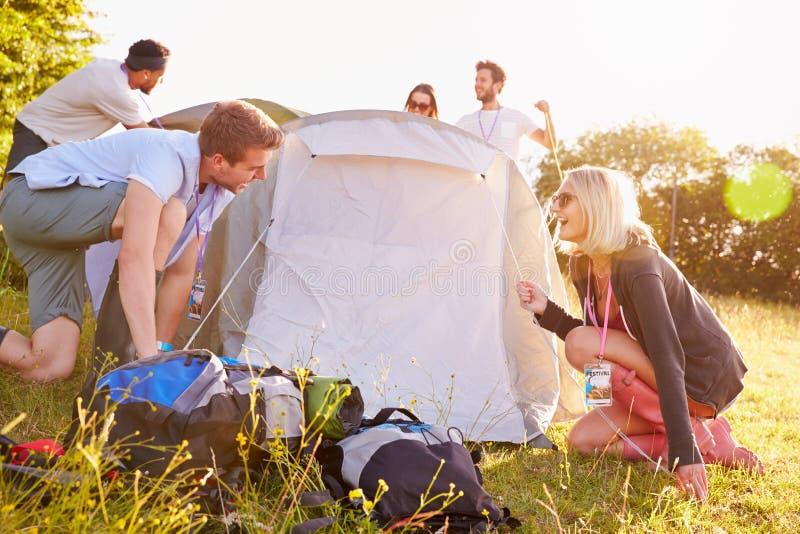 投帐篷的小组年轻朋友野营假日 图库摄影