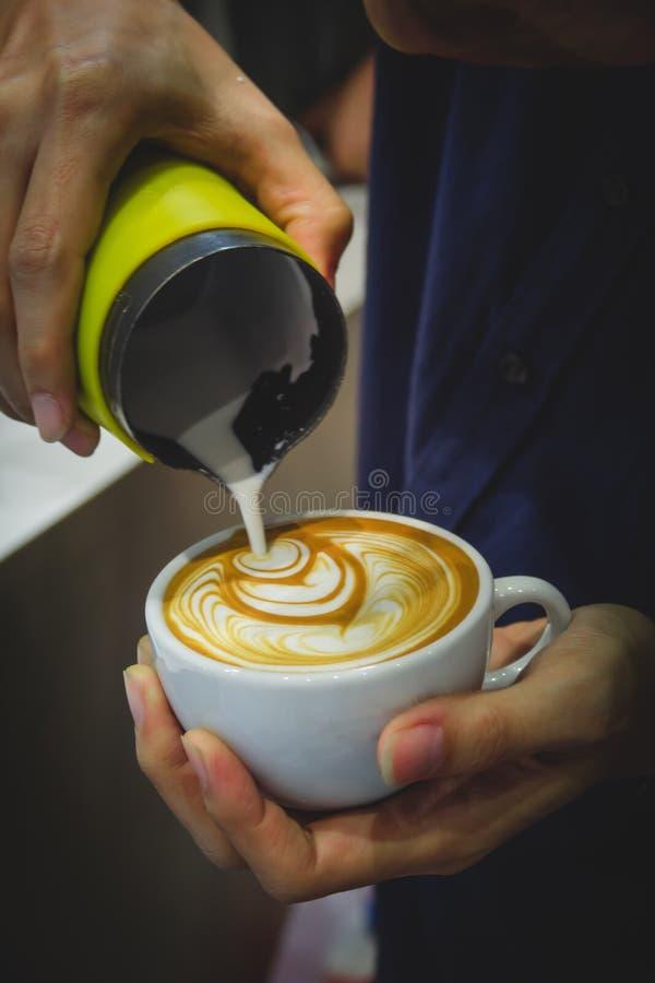 从投手的Barista倾吐的牛奶到做latt的一杯咖啡 库存图片