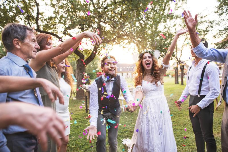投掷五彩纸屑的新娘、新郎和客人在结婚宴会外面 库存图片