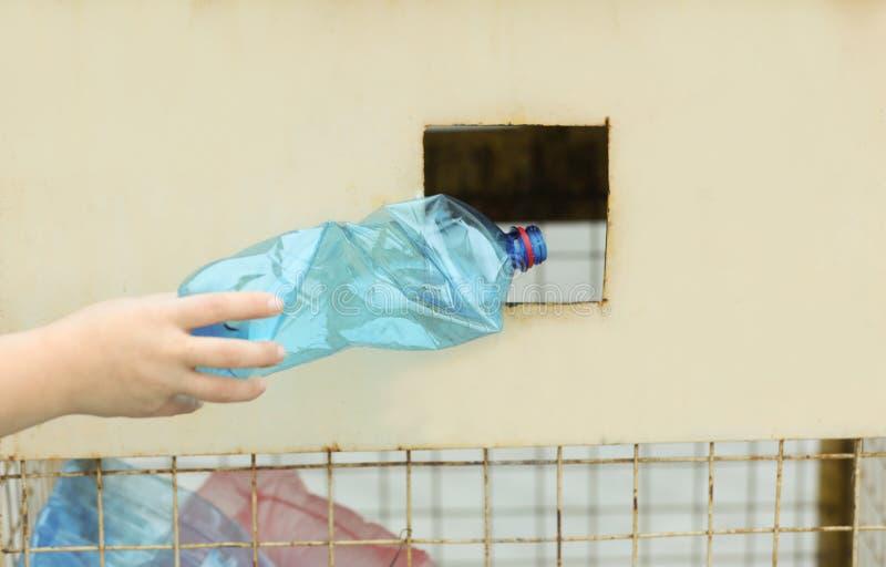 投掷使用的塑料瓶的妇女入在街道上的回收站 免版税库存图片
