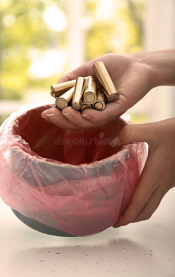 投掷使用的电池的妇女入回收站,特写镜头 库存图片
