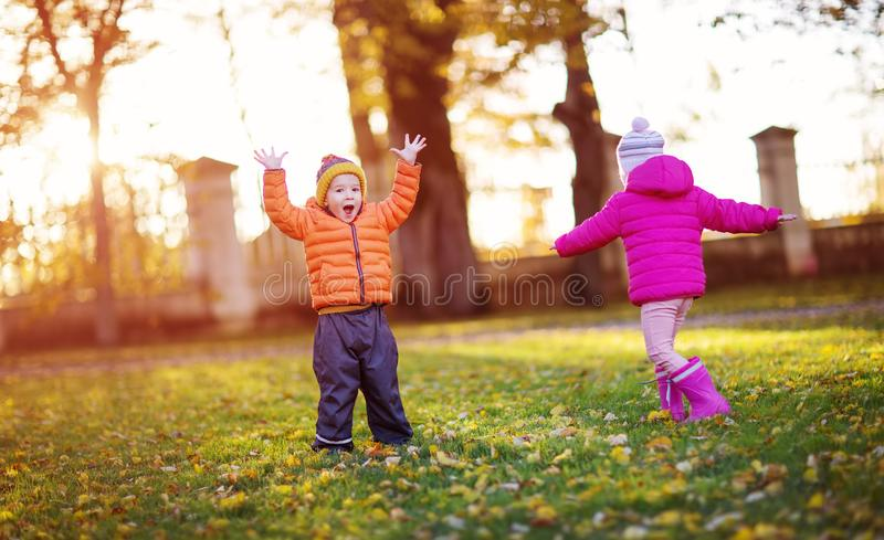 投掷叶子的孩子在美好的秋季天 免版税库存图片