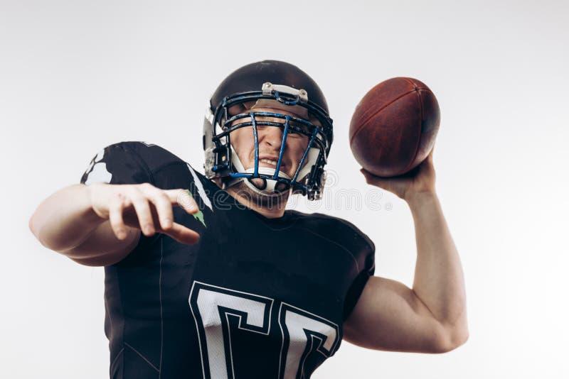 投掷在一场职业橄榄球比赛的四分卫橄榄球 免版税库存图片