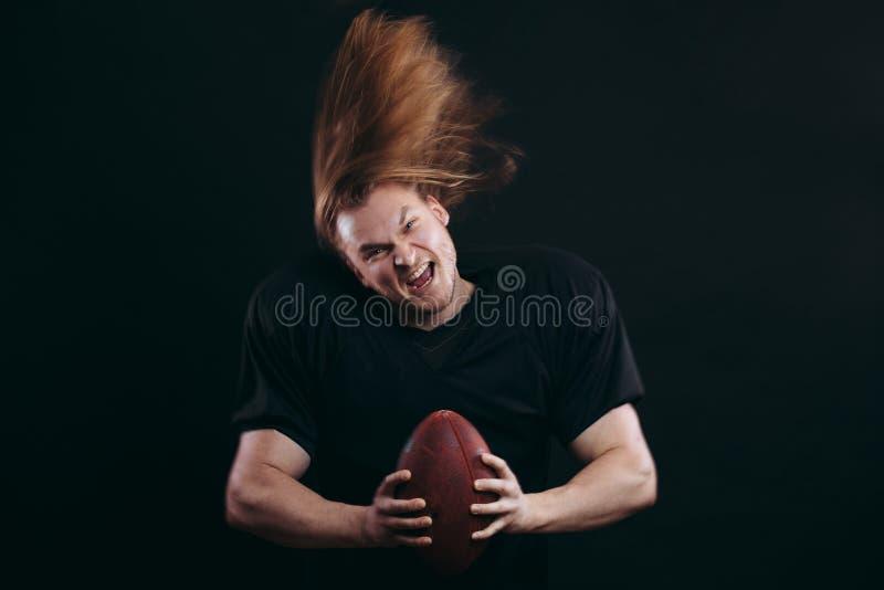 投掷在一场职业橄榄球比赛的四分卫橄榄球 免版税库存照片