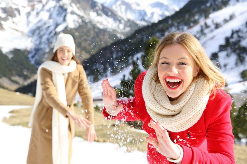投掷在一座多雪的山的朋友雪球在冬天 免版税库存照片