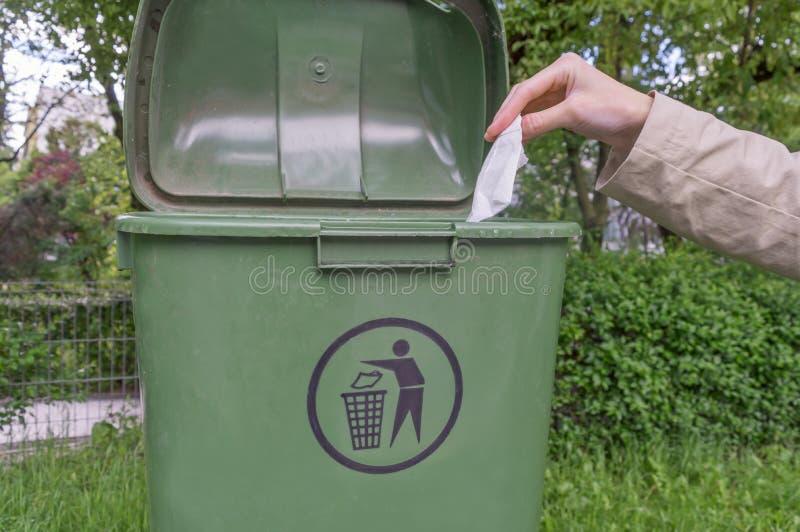 投掷在容器的妇女手压皱纸 库存图片