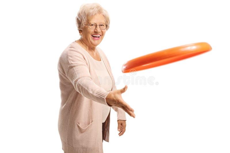 投掷塑料圆盘的快乐的年长妇女 库存照片