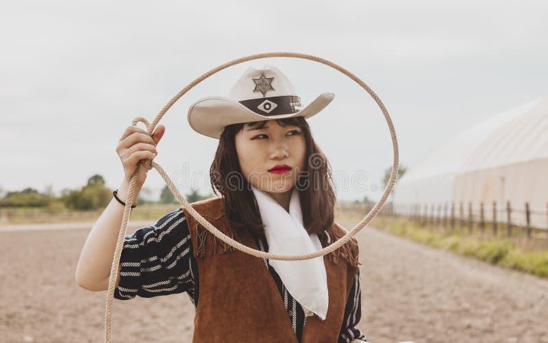投掷套索的俏丽的中国女牛仔在马小牧场 免版税库存照片