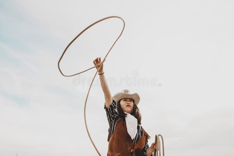 投掷套索的俏丽的中国女牛仔在马小牧场 图库摄影