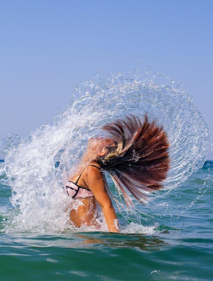 投掷她的在空气的美丽的女孩湿头发,当海游泳时 库存照片