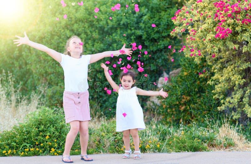 投掷桃红色瓣的女孩在头顶上 免版税库存照片