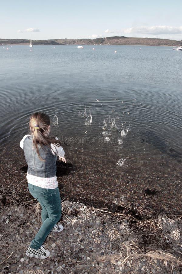投掷水年轻人的女孩石头 免版税库存图片