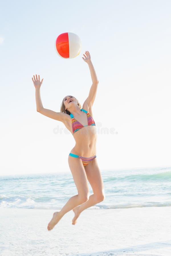 投掷海滩球的美丽的少妇 免版税库存照片