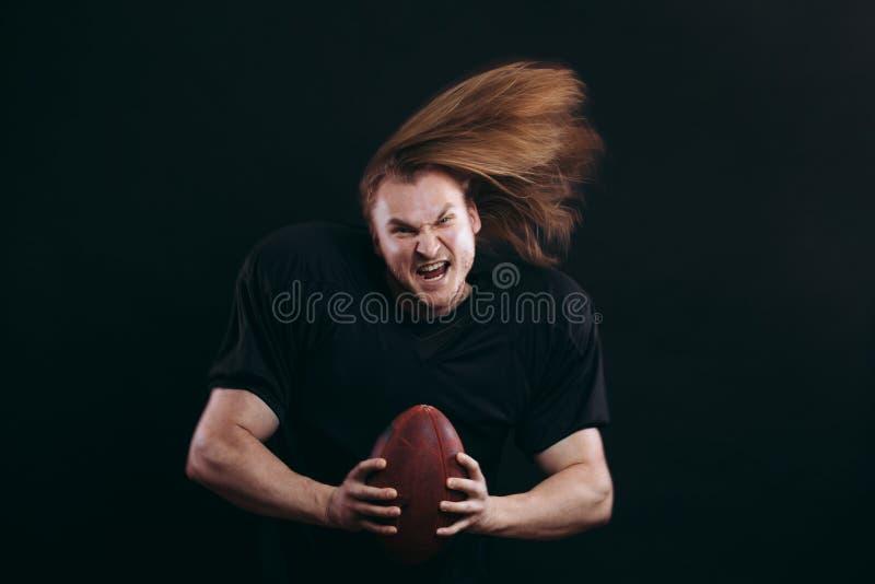 投掷球的美国橄榄球运动员 免版税库存照片