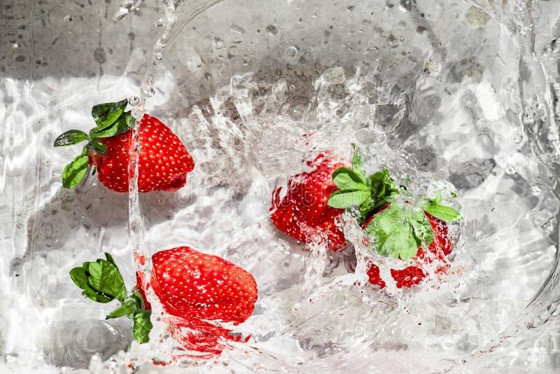 投掷的草莓红色到水里 免版税库存照片