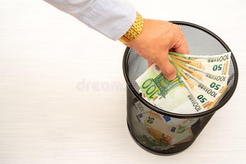 投掷的金钱到垃圾里 免版税库存照片