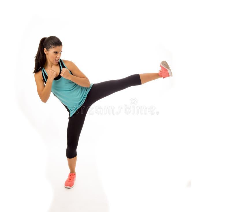 投掷积极的反撞力攻击的战斗和脚踢拳击训练锻炼的年轻可爱和愤怒的拉丁体育妇女 库存照片