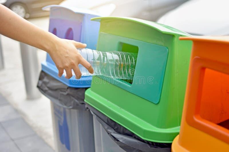 投掷空的塑料瓶的手入垃圾回收 免版税库存照片