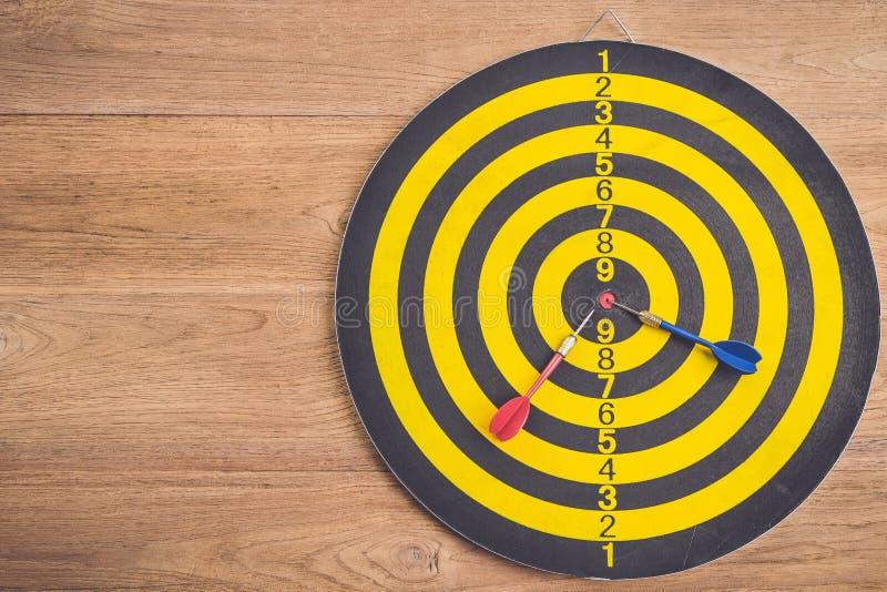 关闭在掷镖的圆靶的中心的射击红色箭箭头并且染黄a.