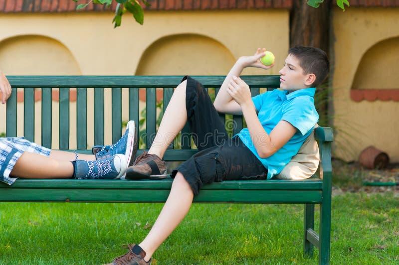 投掷网球的两个十几岁的男孩室外在春天 库存照片