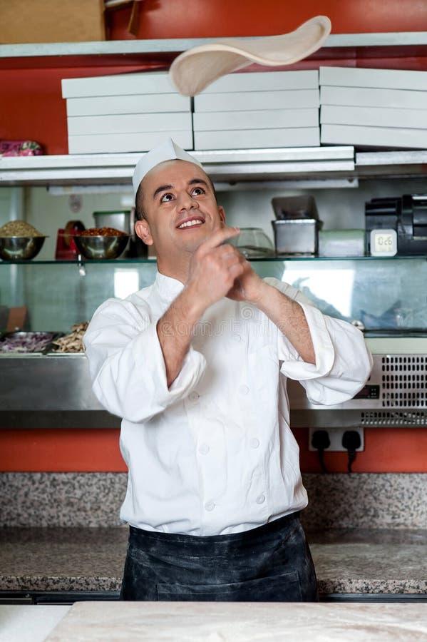 投掷薄饼基地面团的厨师 免版税库存图片
