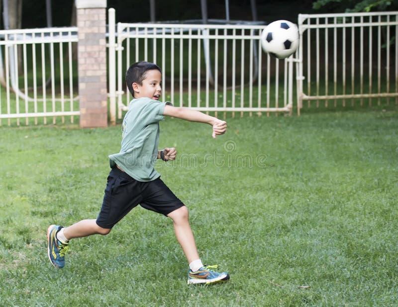 投掷足球男孩的男孩 免版税库存照片