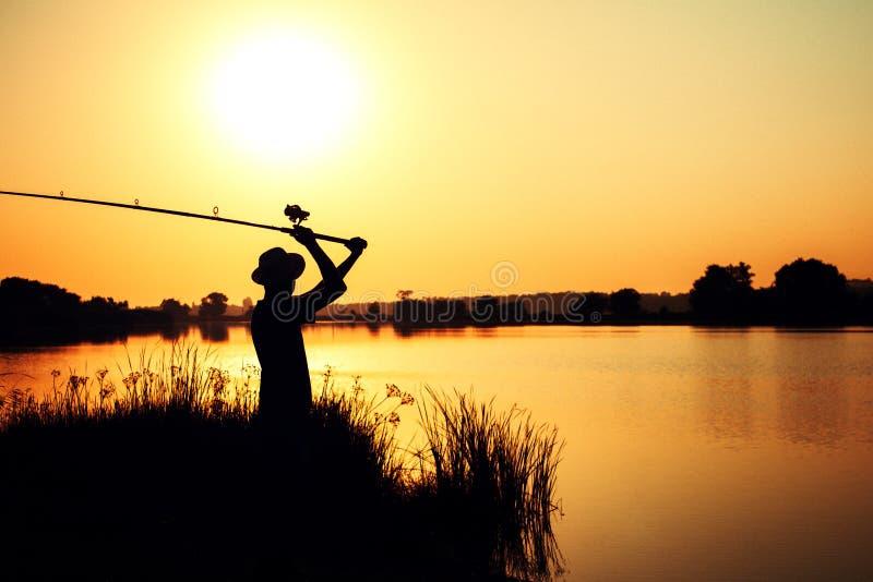 投掷饲养者的渔人的剪影入河 免版税库存图片