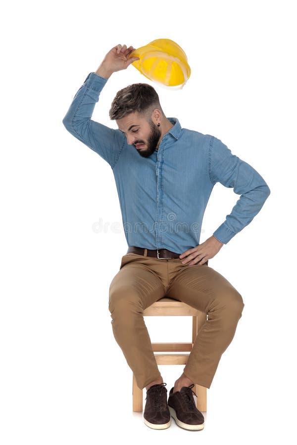 投掷黄色安全帽的蓝色牛仔裤衬衣的不满意的人 图库摄影