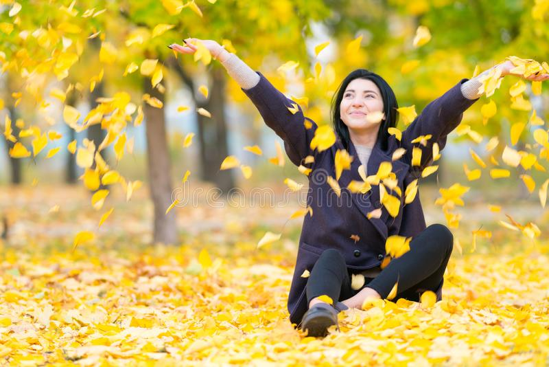 投掷黄色秋叶的愉快的年轻女人 库存图片