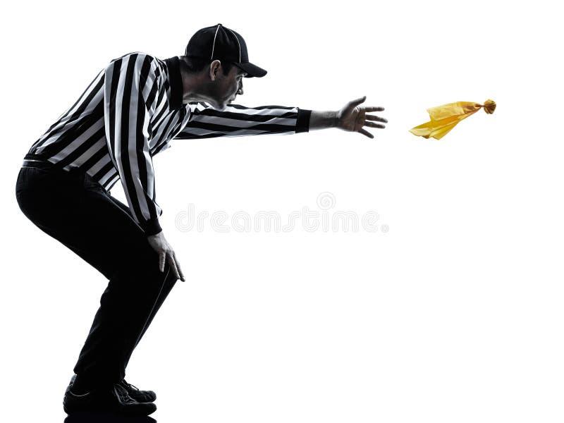 投掷黄旗剪影的橄榄球裁判员 免版税库存照片