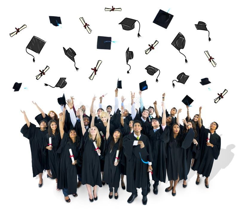 投掷他们的毕业帽子的毕业生 免版税库存照片