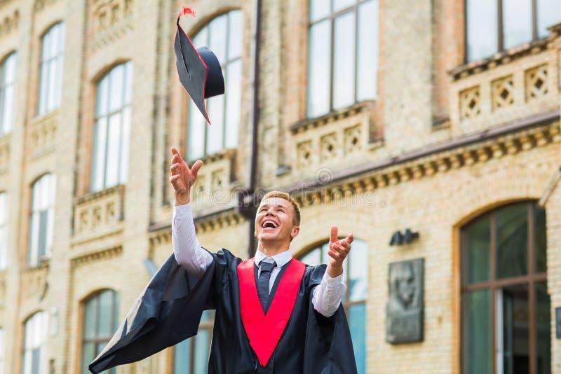 投掷他的灰泥板的愉快的毕业人 图库摄影