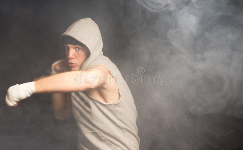 投掷他的重量的年轻拳击手在拳打后 免版税库存图片