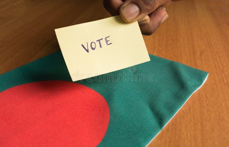 投票的概念-在孟加拉国旗子的人藏品手书面投票的贴纸 图库摄影