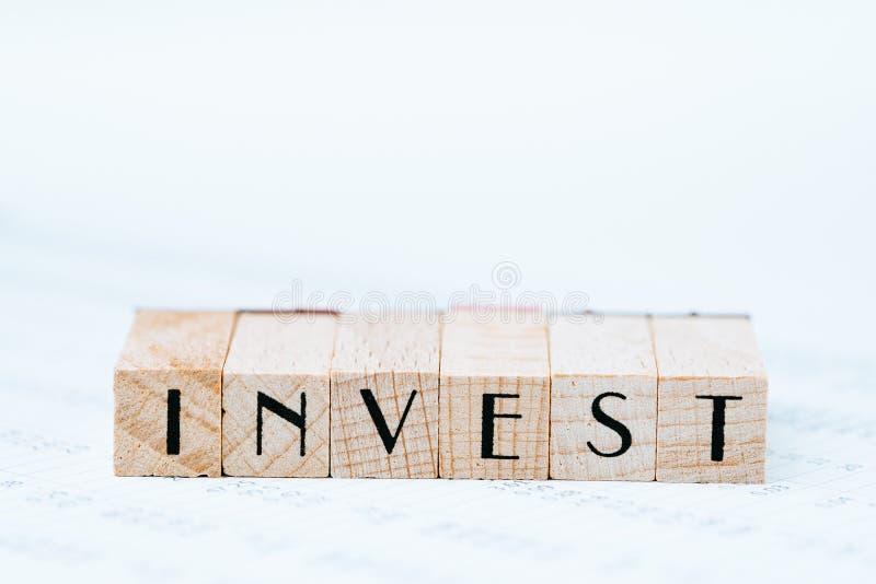 投资、股票、债券或产权概念、笔和木邮票块安排词对资产价数字桌报告投资 免版税库存图片