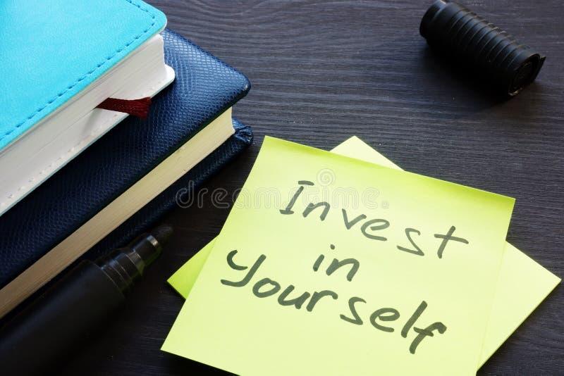 投资在你自己 备忘录棍子和笔记本 库存照片