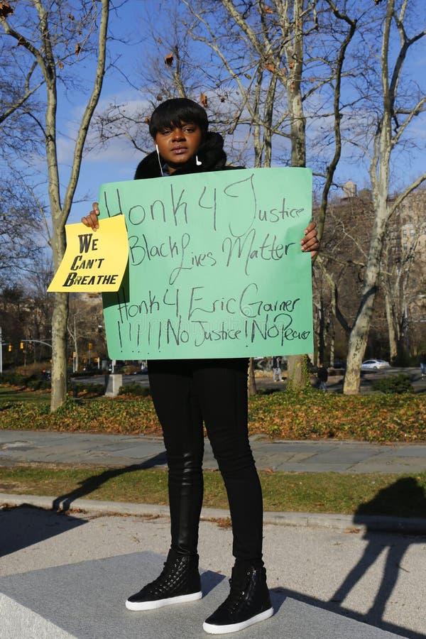 抗议者举行一个标志在行军期间反对警察的残酷行为和关于埃里克谷仓事例的大陪审团决定在盛大军队广场 免版税库存照片