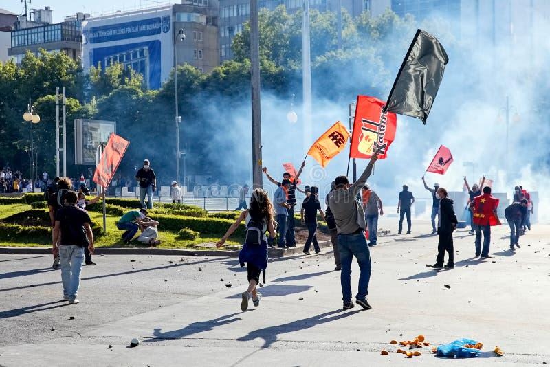 抗议者进位标志在用催泪弹盖的街道上前进在Gezi公园抗议期间在安卡拉,土耳其 库存图片