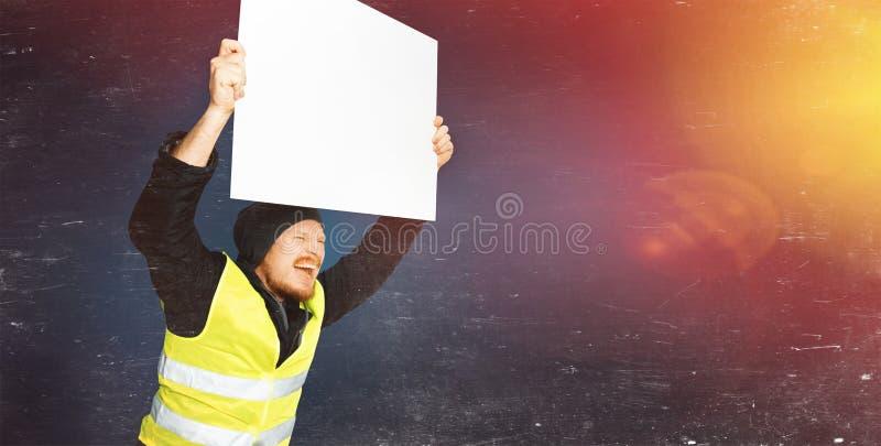 抗议黄色背心 年轻人拿着与光的一张海报在蓝色背景 免版税库存图片