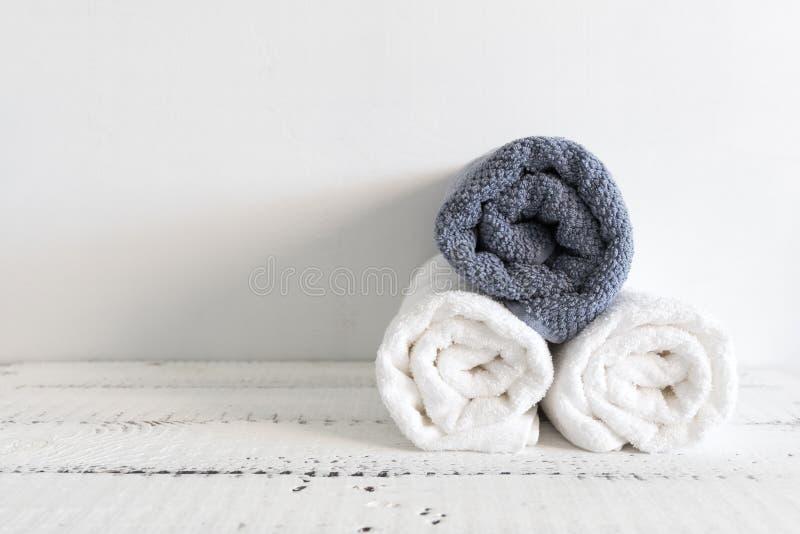 折叠在一张白色木桌上的两块白色和一灰色毛巾 温泉和健康,棉花特里纺织品 生态题材 图库摄影