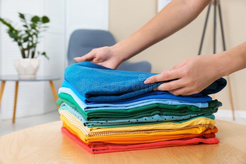 折叠在桌上的妇女明亮的衣裳户内 免版税库存图片