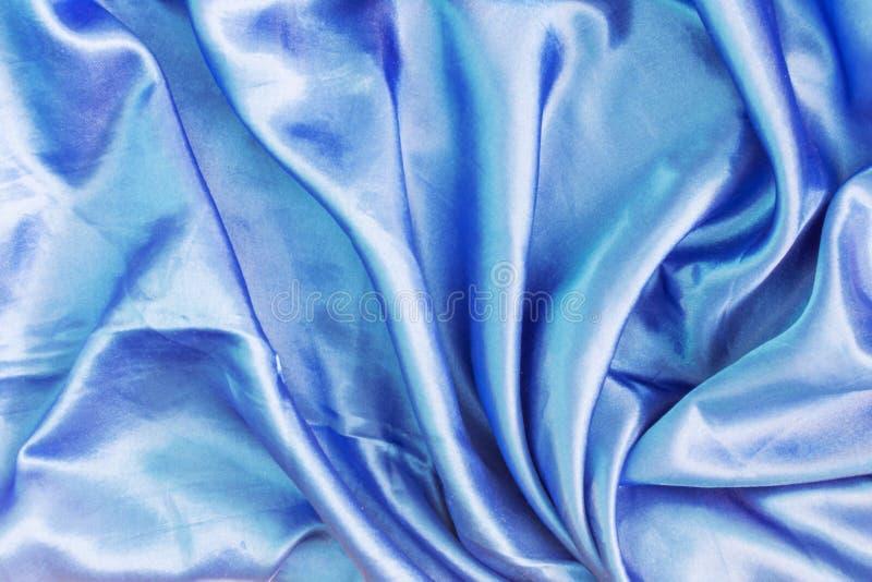 折叠深蓝丝织物的纹理 布局的抽象背景 免版税库存图片