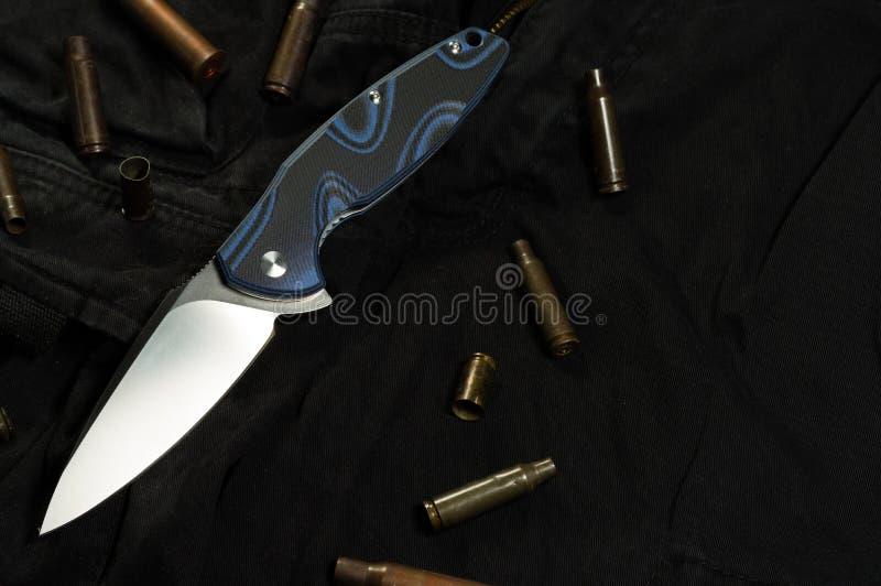 折叠的小折刀和袖子 弹药筒和枪袖子 免版税库存照片