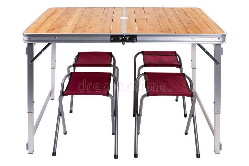 折叠的野餐桌,在一个高位置的集合,那里是椅子在桌下,在白色背景 免版税库存照片