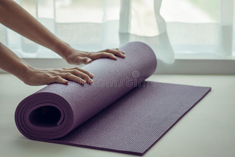 折叠紫色瑜伽或健身席子的妇女的手以后解决 免版税库存照片