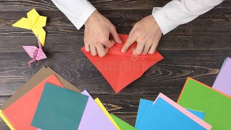 折叠红色纸板料的男性手 免版税库存照片