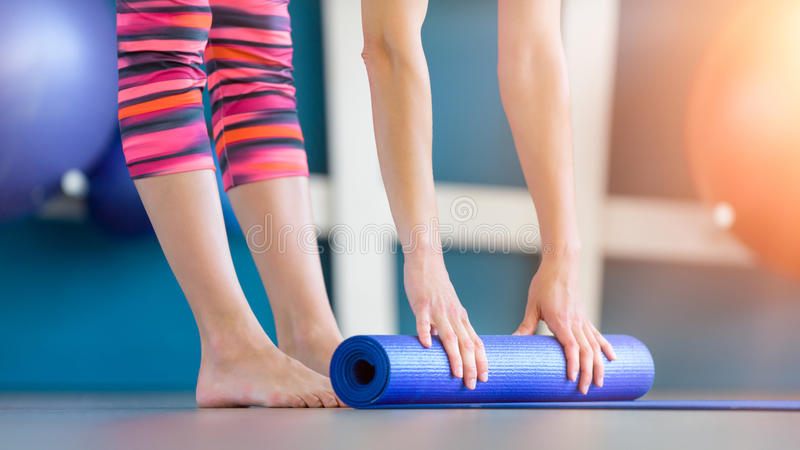折叠蓝色瑜伽或健身席子的少妇在解决以后 免版税库存照片