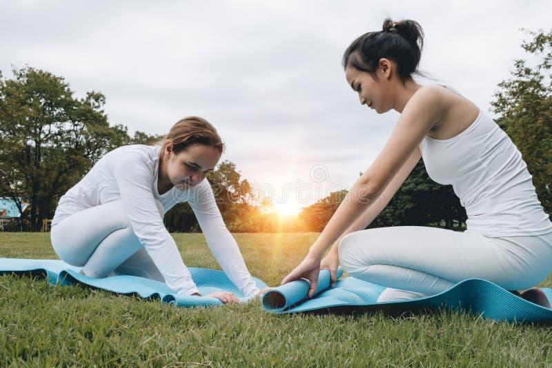 折叠蓝色瑜伽或健身席子afte的两个可爱的少妇 图库摄影